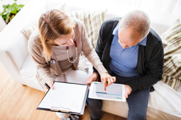 Woman helping senior man with finances on clipboard and tablet.